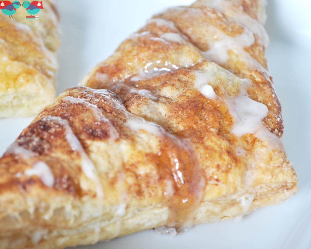 Glazed Apple Turnovers - Turnovers are the perfect pastry to serve as breakfast or dessert! It has the perfect flaky crust and a sweet, delicious apple filling. From The Love Nerds {https://thelovenerds.com}
