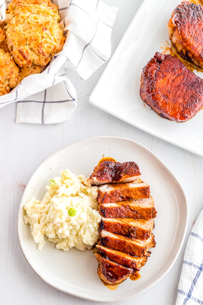 Sliced boneless pork chop with a brown sugar glaze sits on a round white plate next to mashed potatoes with a basket of biscuits in the top left corner and a plate with more pork chops in the top right corner