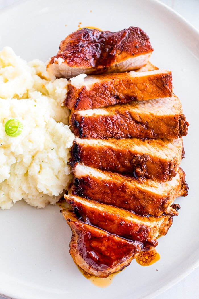 UPCLOSE PHOTO OF BROWN SUGAR PORK CHOP SLICED INTO 7 PIECES ON A WHITE PLATE NEXT TO A SIDE SERVING OF MASHED POTATOES