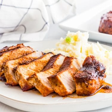 Round white plate with raised lip with a pork chop sliced into 7 pieces in front of a pile of mashed potatoes