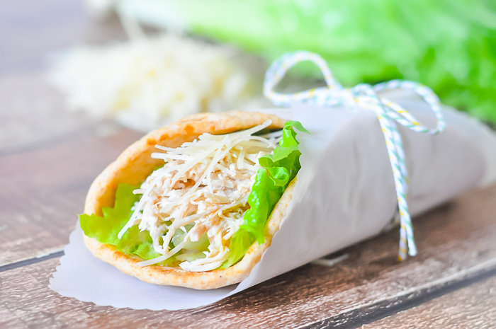 Shredded Caesar Chicken inside a pita with romaine lettuce all wrapped up in parchment paper with ribbon and twine