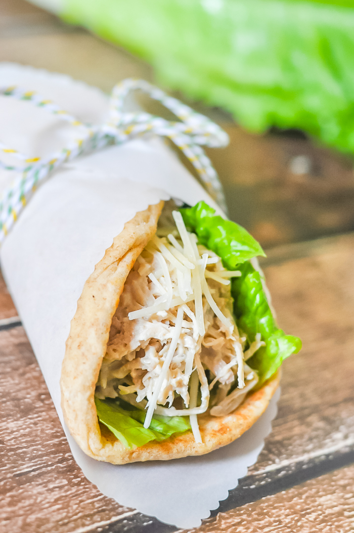 Close up of chicken caesar pita with lettuce and parmesan cheese wrapped in parchment paper and tied off with a piece of twice with romaine lettuce in the background