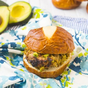 Turkey burger with chopped avocado inside sits on a pretzel bun on top of a blue and green floral napkin with extra avocado sits in the back left corner