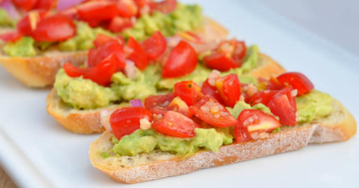 A fresh and light appetizer recipe that everyone will love - Avocado Bruschetta Crostinis! Plus, they're easy to make.   The Love Nerds