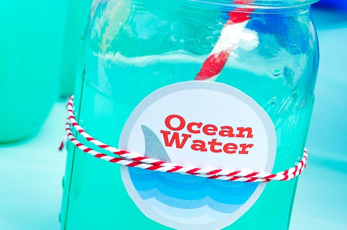 "Mason jar with bright blue punch and a round label with waves, a shark fin and the words ""Ocean water"" on it tied on by red and white bakers twine. A red and white striped straw sits in the jar."