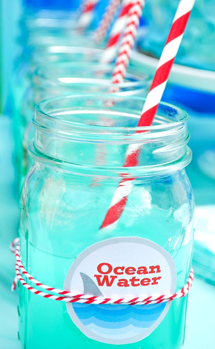 A row of mason jars with red and white patterned straws are filled with aqua blue punch and labeled with a round label with waves, shark fins, and the words ocean water.