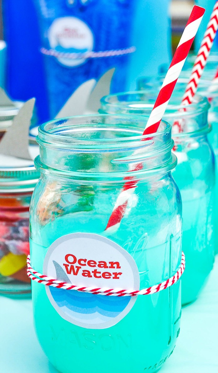 A row of ocean water blue punch in mason jars is on the right side of the picture with red and white straws with smaller mason jars with paper shark fins sit on the left side of the photo with ocean gummies as favors.