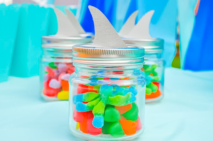 Colorful gummy candies inside mini mason jars with a paper cut out shark fin on the top