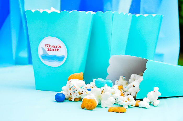 Aqua Blue popcorn boxes labeled as Shark Bait sits in a row with one tipped over and its contents laying in front on the table - popcorn, goldfish, blue chocolates and sprinkles.