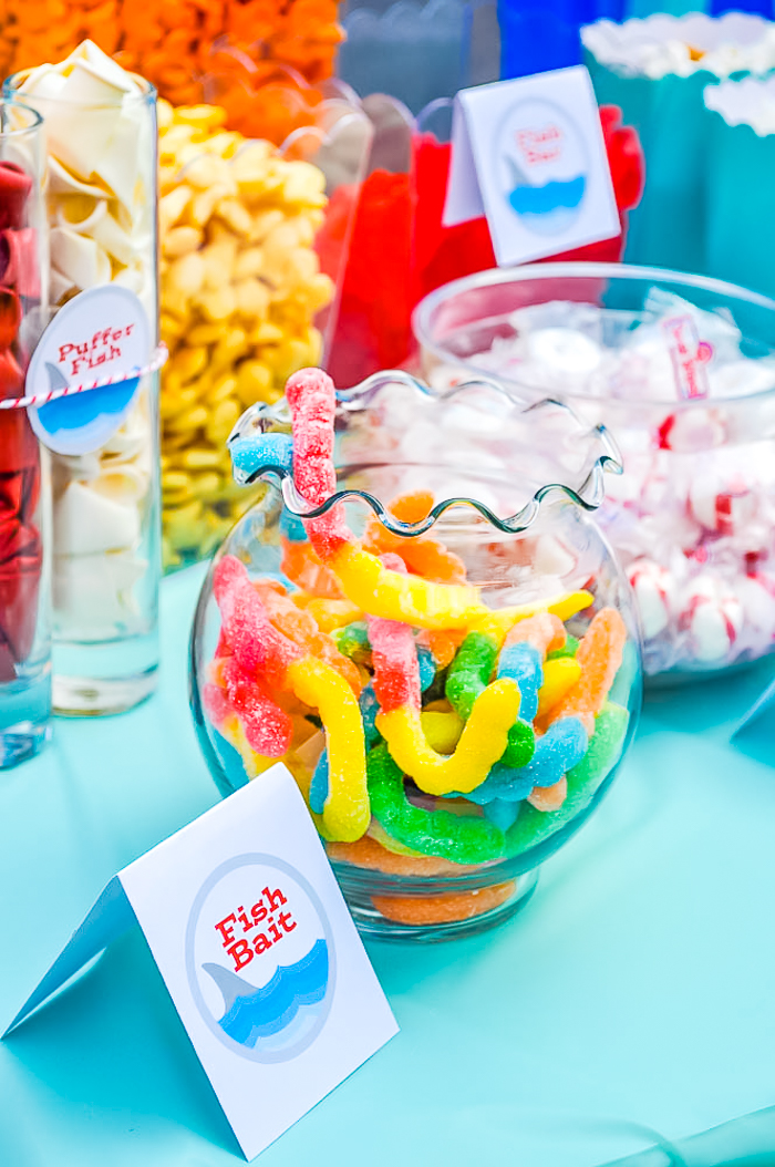 Glass jars sitting on an aqua blue tablecloth filled with colorful gummy worms, red and white peppermints, white and orange gold fish, and red swedish fish for an ocean themed party