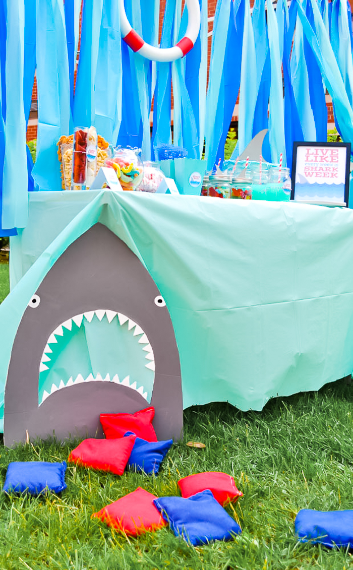 Shark Head with a large open mouth rests on grass with bean bags in front. A table with aqua blue table cloth sits behind it with food, drinks, and a sign that says Live Every Week Like Shark Week.