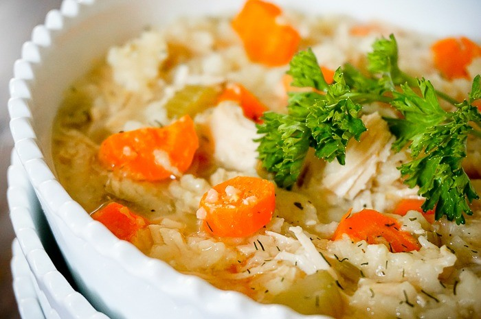 a stack of bowls is filled with a chicken noodle soup recipe with slices of carrots easily visible on top and a garnish of fresh parsley.