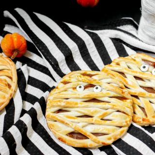 Trick or Treat! Pumpkin Mummy Hand Pies make an adorable Halloween dessert! Plus, they're an easy recipe to serve and take with you! | The Love Nerds