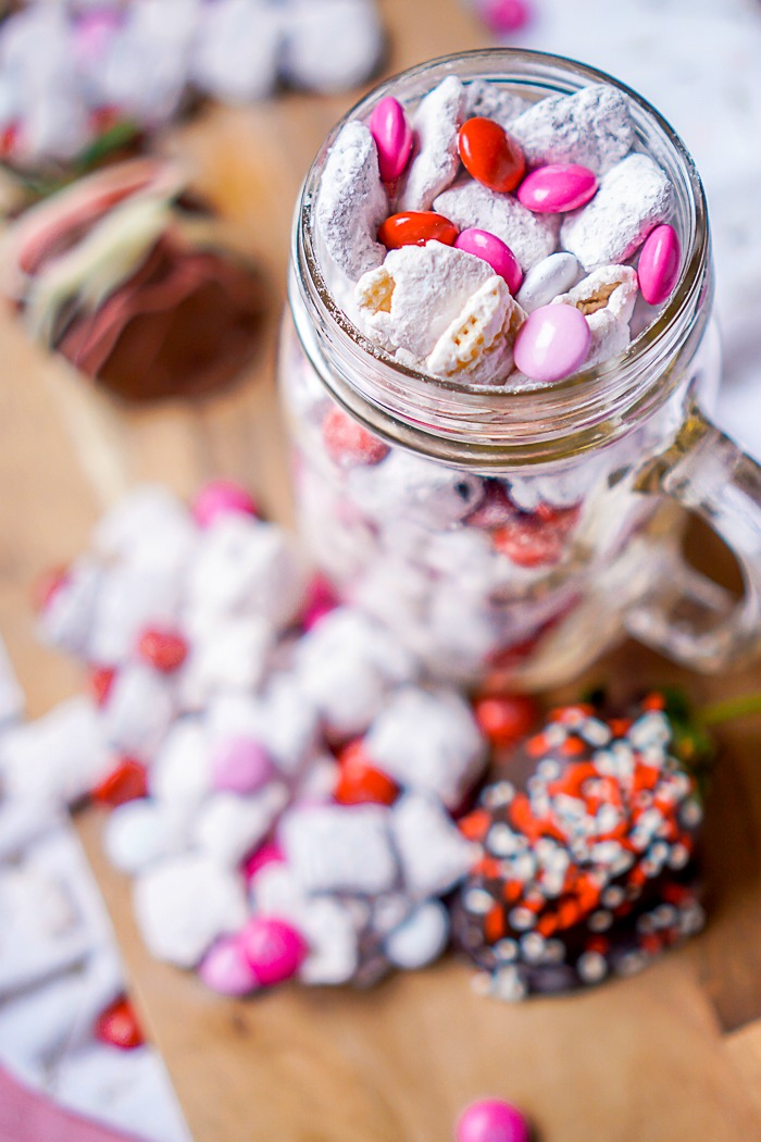 This muddy buddies recipe is the perfect Valentine's Day party treat! Try this delicious Chocolate Covered Strawberry Puppy Chow with chex mix, milk chocolate, white chocolate, strawberry cake mix, and powdered sugar!