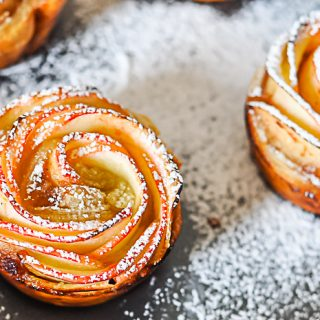 An apple rose pastry is definitely a statement piece for your holiday table! Apple Roses are gorgeous enough for Thanksgiving dessert or Christmas breakfast but easy enough to make anytime. With a dusting of powder sugar, everyone is going to love them! | The Love Nerds #appledessert #holidaydessert #holidaybreakfast #applepastry