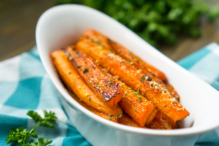 White oval bowl is filled with halved carrots that are coated in parmesan and other spices
