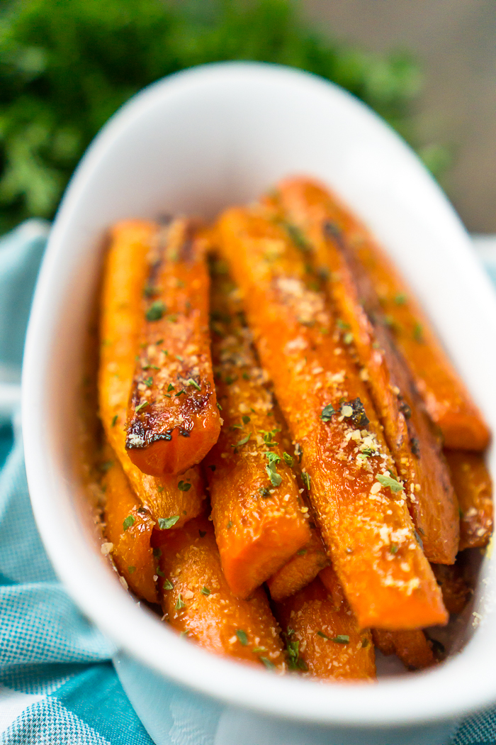 Oven Roasted Brown Sugar Carrots are an easy holiday side dish and are featured in a white oval scoop bowl.