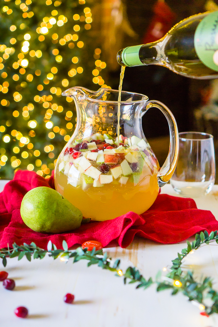 A PITCHER OF WHITE WINE HOLIDAY SANGRIA SITS IN FRONT OF A CHRISTMAS TREE OUT OF FOCUS WHILE A BOTTLE OF SPARKLING WINE IS POURED IN BEFORE SERVING