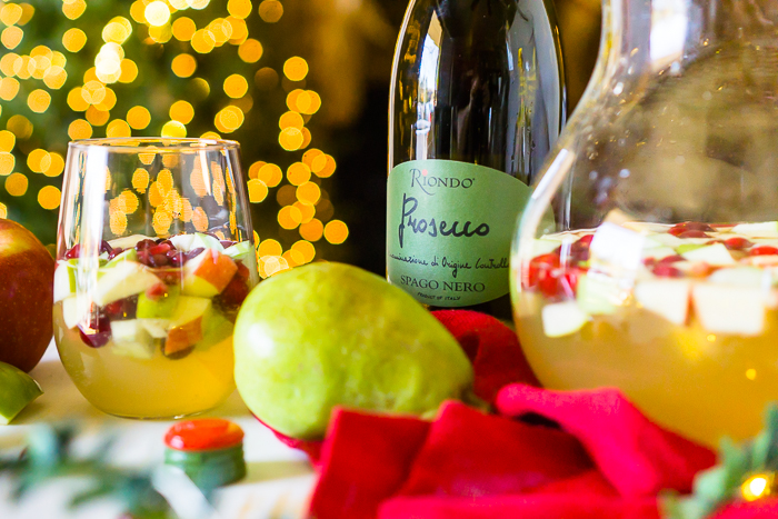 A WHITE WINE HOLIDAY COCKTAIL MADE WITH SPARKLING WINE SITS ON A HOLIDAY TABLE WITH GREENERY AND LIGHTS.
