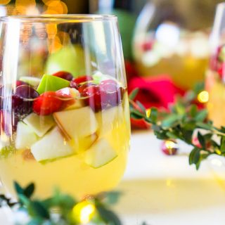 I'm dreaming of a White Christmas Sangria, filled with tasty red and green fruit for a festive holiday cocktail! Just fill up the sangria pitcher with red and green apples, pears, cranberries and pomegranates and some white wine and prosecco, too, of course! Lightly sweet and tangy fruit makes a Christmas Sangria Recipe your guests will love!