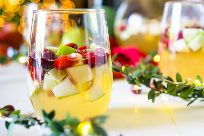A WHITE WINE SANGRIA IN A STEMLESS GLASS FILLED WITH RED AND GREEN APPLES, FRESH CRANBERRIES AND POMENGRATES SITS IN FRONT OF A PITCHER AND OTHER GLASSES WITH CHRISTMAS LIGHTS IN THE BACKGROUND OUT OF FOCUS