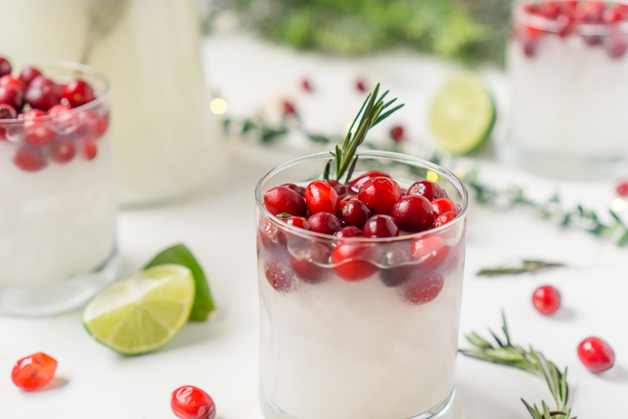 Low cocktail glass is filled with creamy white cranberry margaritas and topped with fresh red cranberries and a rosemary garnish with a pitcher and other glasses resting in the background out of focus amongst Christmas lights and greenery