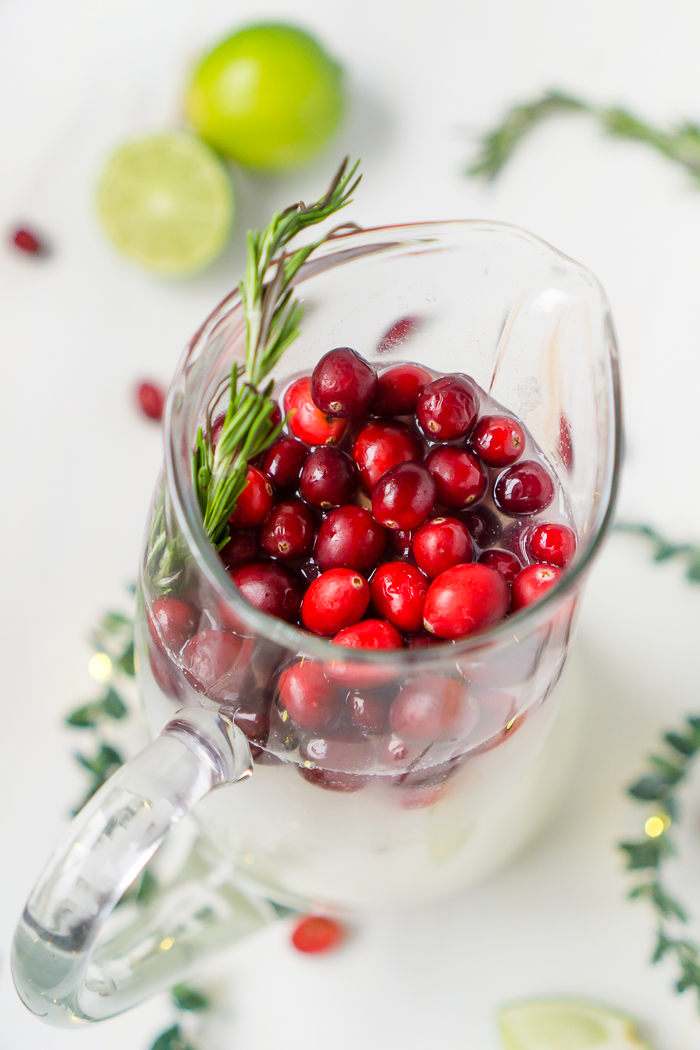 A tall glass pitcher of Christmas Margaritas sits on a white wood table and garnished on the top with red cranberries and a sprig of rosemary