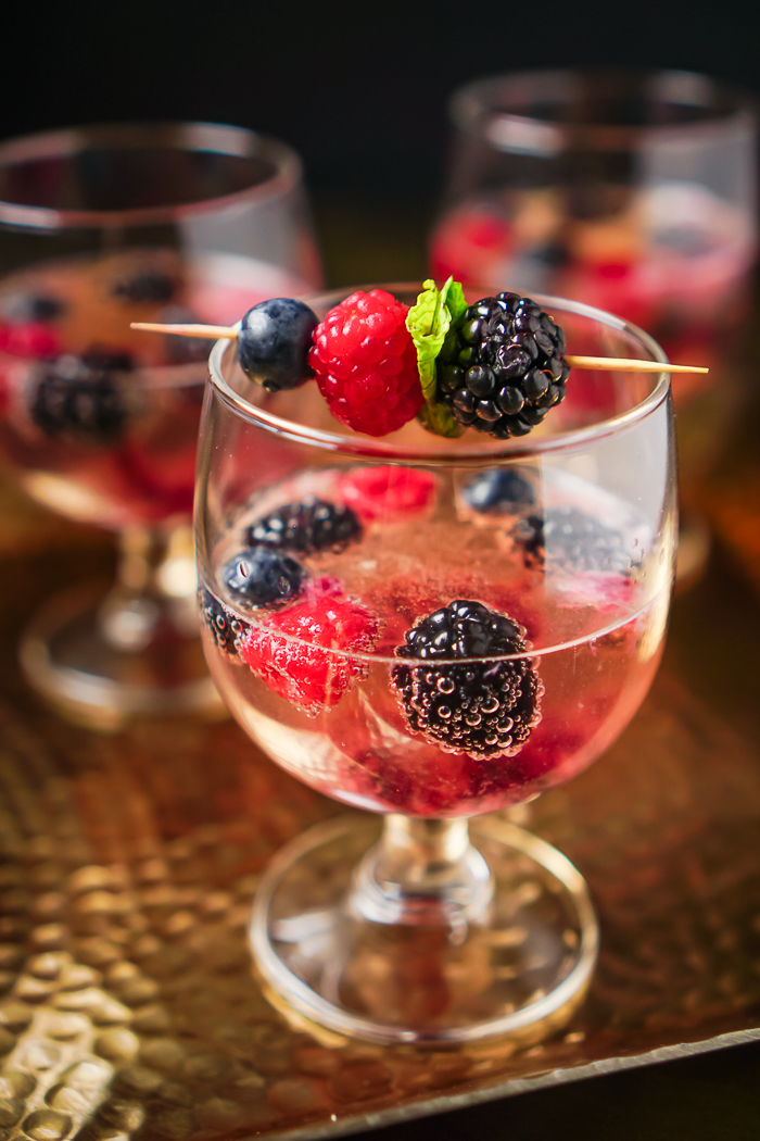 Toast your holiday festivities with a Berry Champagne Cocktail. Lightly sweetened with blackberries, blueberries and raspberries with a gorgeous first impression for your holiday parties. Just think how pretty your midnight toast could be with this as your New Year's Eve cocktail!  | The Love Nerds #newyearsdrinks #champagnecocktailrecipes