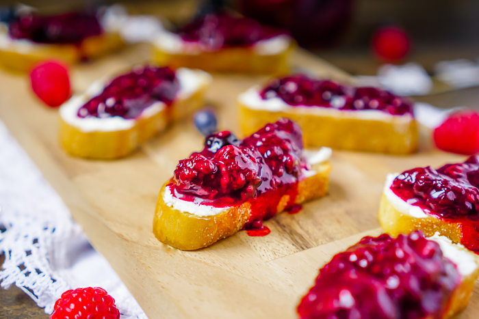 This Berry Goat Cheese Crostini recipe is an easy goat cheese appetizer that provides the perfect combination of creamy goat cheese, sweet three berry jam and a crunchy homemade crostini.