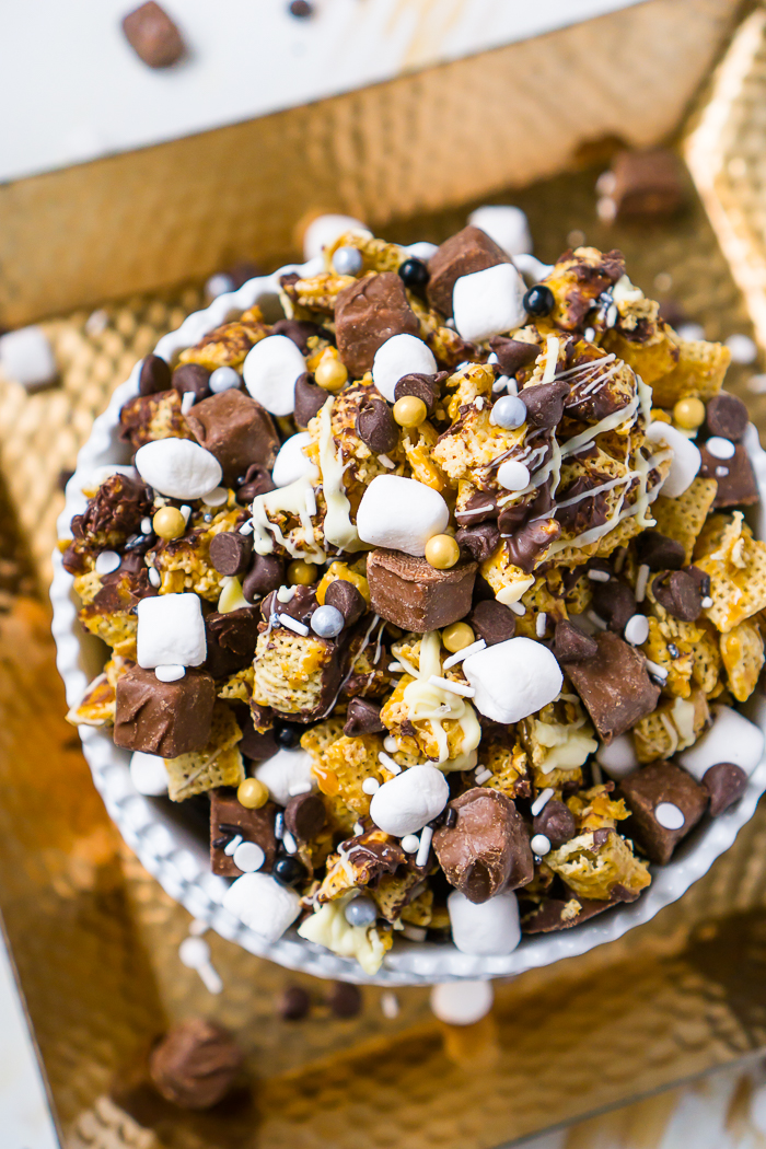 Double Chocolate Caramel Sweet Snack Mix is an easy dessert party recipe! Chex Mix topped with caramel, chocolate and white chocolate party mix recipe is topped with candy bites, marshmallows, New Year's Eve sprinkles and even more chocolate!