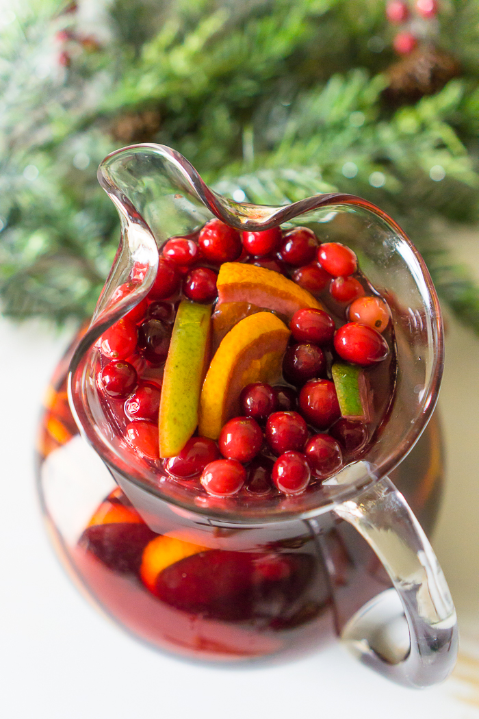 A LARGE GLASS PITCHER FILLED WITH RED WINE CHRISTMAS SANGRIA WITH LOTS OF FRUIT FLOATING AT THE TOP INCLUDING PEARS, ORANGES, AND CRANBERRIES