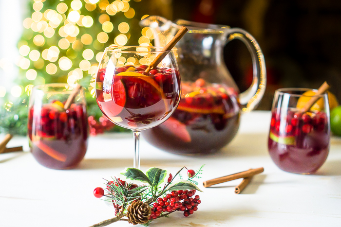 SPECIAL RED HOLIDAY SANGRIA WITH CRANBERRIES, ORANGE AND APPLES WITH A CINNAMON STICK GARNISH