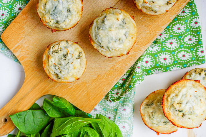 A WOOD CUTTING BOARD SITS ON A GREEN FLORAL NAPKIN WITH SPINACH DIP MUFFINS RESTING ON TOP