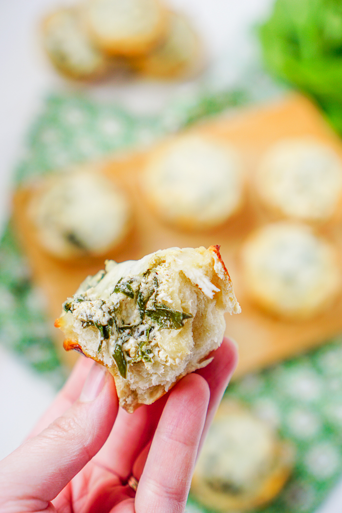 A SPINACH DIP MUFFIN TORN OPEN SHOWING CREAMY SPINACH FILLING! MAKES THE PERFECT GAME DAY APPETIZER