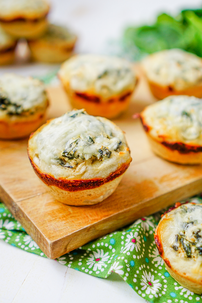 A WOOD BOARD FULL OF INDIVIDUAL SPINACH DIP BREAD BOWLS COOKED IN A MUFFIN PAN