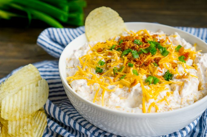 Everyone needs to have their go-to easy chip dip recipe for parties and get togethers, and this loaded potato dip recipe is mine! Add classic baked potato toppings to a sour cream chip dip base and serve on your favorite potato chip. Mix together this party appetizer in 5 minutes and enjoy!