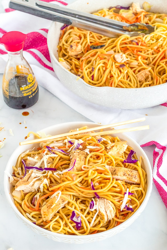 A big white pasta bowl is filled with chicken lo mein with cabbage, carrots and onions with a set of chopsticks rest on the side of the bowl with a skillet full of lo mein sitting in the top right and a bottle of half empty soy sauce sitting on the white marble countertop