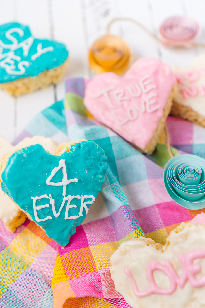 Heart Shaped Rice Krispie Treats coated in chocolate and decorated with Valentine's Day sayings like Pick Me, True Love, and Kiss! A fun Valentine's Day Treats the kids will love decorating!