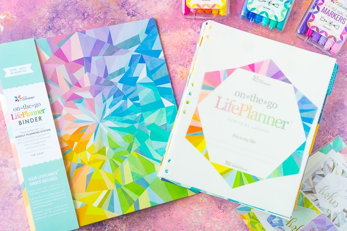 Erin Condren Life Planner Binder in colorful kaleidoscope design with the inside calendar filling sitting to the right of the binder
