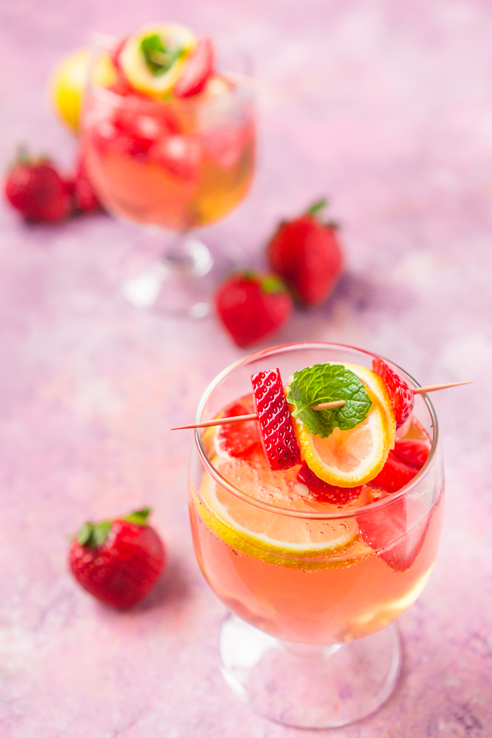 Two wine glasses filled with a rose wine spritzer and garnished with fresh strawberries and lemons.