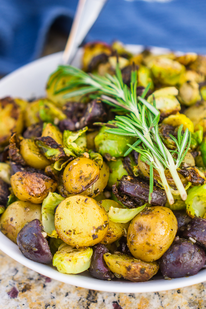 White Bowl filled with grilled purple and yellow potatoes and fresh brussels sprouts