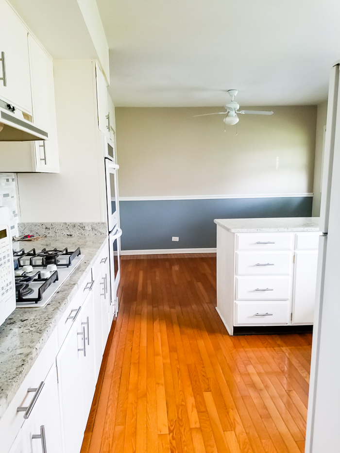 Partially updated white kitchen with white appliances.