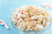White Chocolate Peppermint Puppy Chow (or Muddy Buddies) combines candy canes and white chocolate for a tasty holiday snack mix that's perfect for your Christmas parties! It also makes a great holiday gift for your neighbors, coworkers and friends! | The Love Nerds