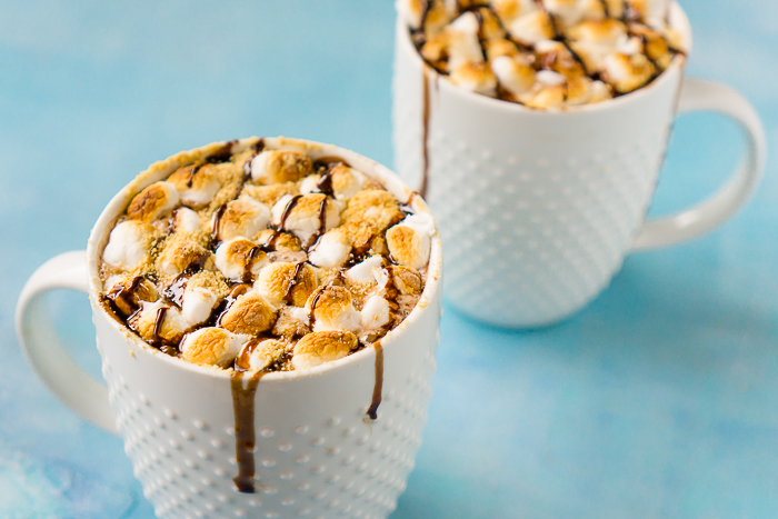 Indulge in an extra rich treat this winter season with this easy S'Mores Hot Chocolate! Rich hot chocolate topped with toasted marshmallows, graham cracker crumbs and chocolate drizzle!