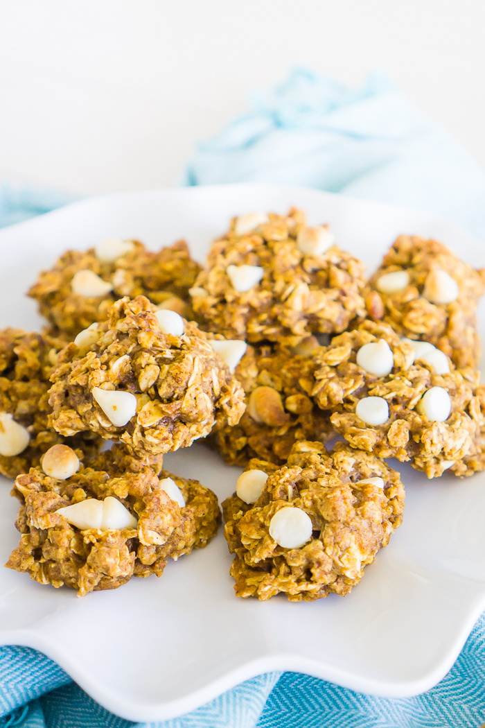 A white plate with wavy edges sits on a blue chevron napkin with a dozen pumpkin oatmeal cookies that have white chocolate chips.