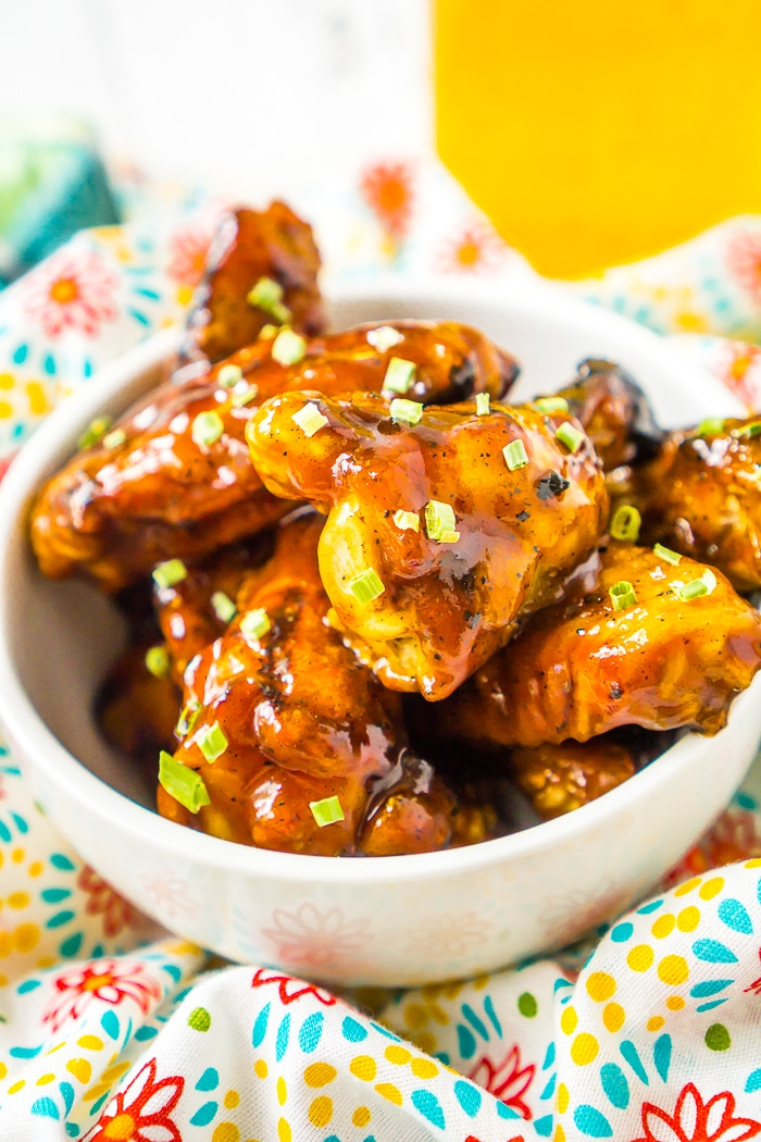 A white bowl is filled with chicken wings covered in a honey bbq sauce and garnished with chives on top.