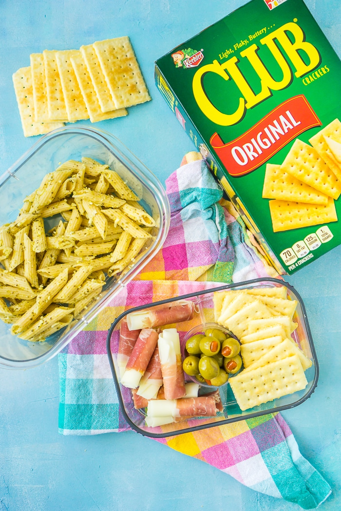 Club cracker box sits next to a clear lunch box with pesto pasta salad, mozzarella wrapped with prosciutto, green olives and crackers.