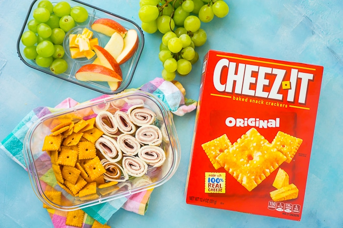 Cheeze-It's box sits next to a bento box filled with green grapes, apple slices, cubed cheese, cheeze-its and a tortilla roll up cut into small bites.
