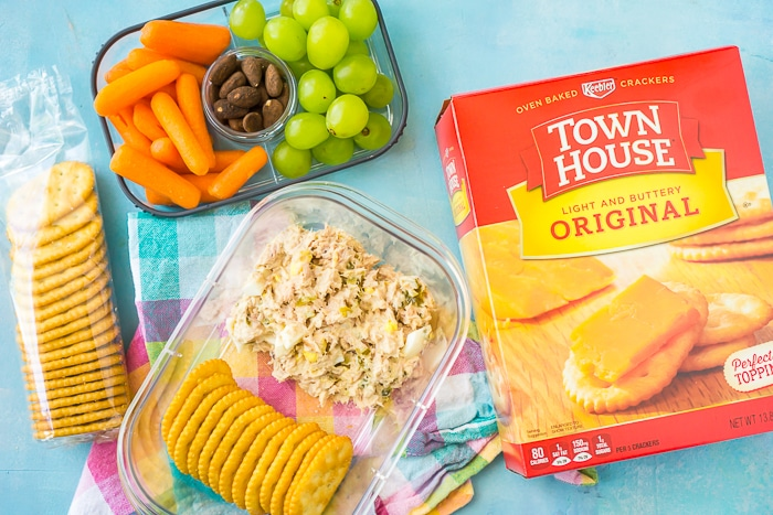 TOwnhouse crackers box sits next to a bento lunch box filled with green grapes, carrot sticks, cocoa roasted almonds, tuna salad and townhouse crackers