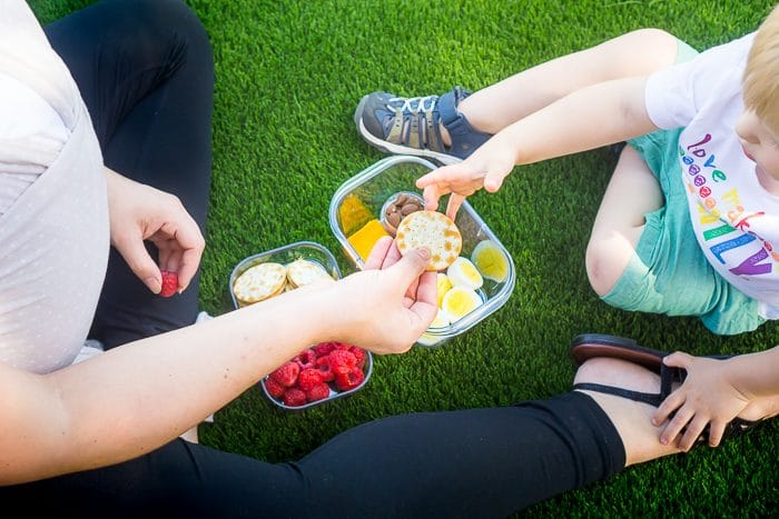 Mom who is wearing a baby in a solly wrap sits on the grass with her toddler son with a bento box snack sitting on the ground between them with cheese, hard boiled egg, raspberries, crackers and more. Son is reaching for a cracker.